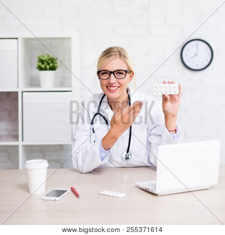 Healthcare And Pharmacy Concept - Young Female Doctor Showing Pills In Modern Office Or Store