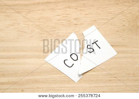 Cut The Word Cost Concept For Recession Or Credit Crisis On Wood. Concept Of Cost Cut.