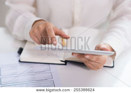 Close-up Of Businesswoman Working With Digital Tablet In Office. Young Caucasian Businesswoman Sitti