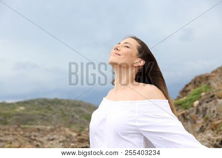 Happy Woman Breathing Fresh Air With A Storm In The Background