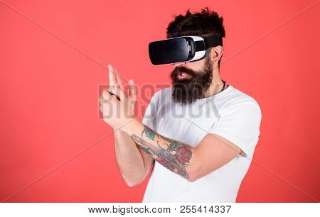 Best shooters for VR. Man bearded hipster with virtual reality headset on red background. First person shooter shows how addictive VR could be. Man hand gesture as gun play shooter game in VR glasses. poster