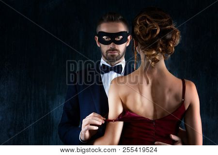 Rich Millionaire Man Male In Black Carnaval Mask Bow Tie And Suit Seduces Tempts Lures Woman Female