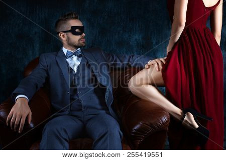 Rich Millionaire Man Male In Carnaval Mask Sitting In Leather Sofa Tempts Touching Leg Of Elegant Wo