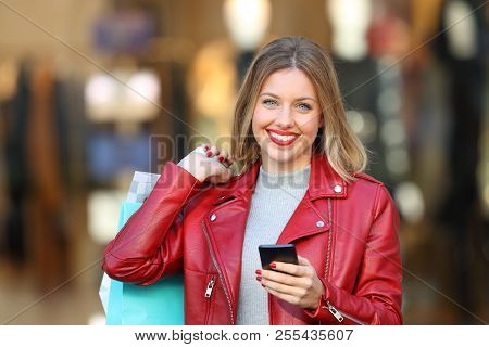 Happy Shopper Posing Holding A Smart Phone And Shopping Bags In The Street With A Storefront In The