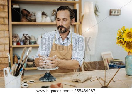 Dark-haired Ceramist Feeling Satisfied During The Process Of Work