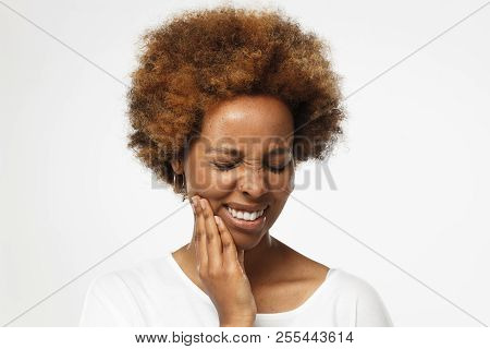 Young African American Woman In Blank White T Shirt, Isolated On Gray Background, Touching Her Face
