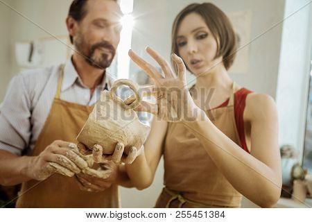 Dark-haired Female Ceramist Improving Her Future Tea Cup