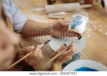Two Ceramists Holding Painting Brushes While Decorating Handiwork