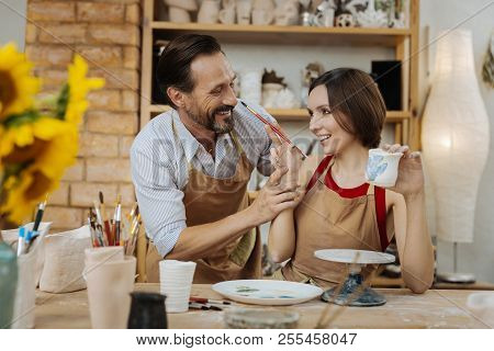 Dark-haired Female Ceramist Having Fun In Workshop With Husband