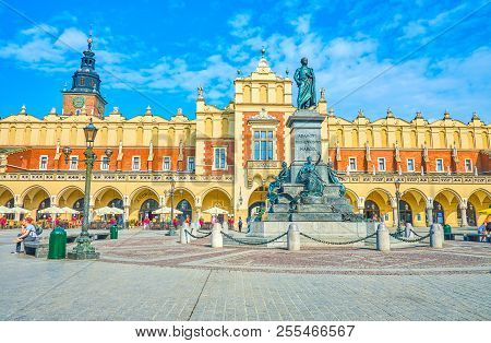 Krakow, Poland - June 11, 2018: The Beautiful Frontage Of Sukiennice With Monument To Adam Mickiewic