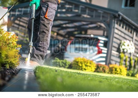 Garden Cleaning Work With Powerful Pressure Washer. Cleaning Cobble Stone Path Elements
