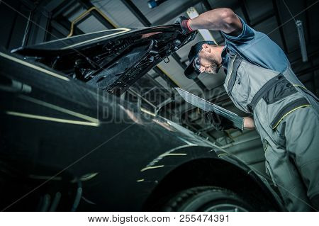 Servicing Modern Car. Pre Owned Vehicle Inside Auto Service. Caucasian Car Mechanic In His 30s Takin