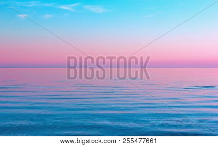 Idyllic Colorful Seascape - The Wavy Surface Of The Water Reflects The Pink And Blue Colors Of The S