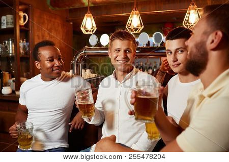 Company Of Four Handsome Men Wearing In White Top And Jeans, Listening Carefully Story Of One Of Men