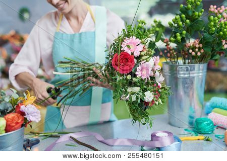 Crop View Of Smiling Florist Snipping Flower Stems