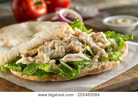 A Delicious Chicken Pita Sandwich With Lettuce And Sauce.