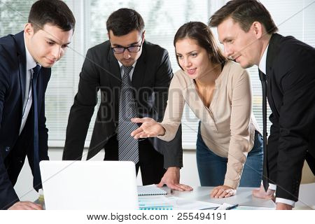Business people stand around the table and discuss the project in the office