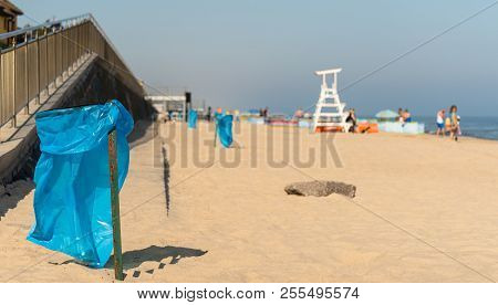 An Empty Garbage Bag On The Beach On A Sunny Summer Day, In The Background People, A Beach Screen An