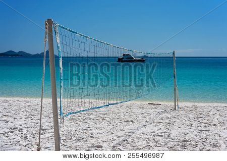 A Badminton Net Set Up For Tourists To Play Ball On Whitehaven Beach With A Leisure Boat In The Back