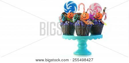 Halloween Candyland Drip Cake Style Cupcakes With Lollipops And Candy On White.