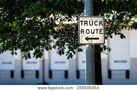 Truck Route Sign On A Steel Post With Trees And Loading Docks In The Background