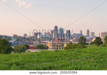 View Of Kansas City, Missouri Skyline At Dusk With Golden Light Shining On The City.  All Registered