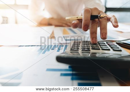 Close Up Business Woman Using Calculator And Laptop For Do Math Finance On Wooden Desk In Office And