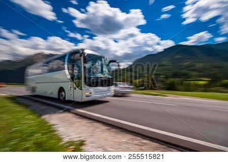 Tourist bus traveling on the road in the background the Dolomites Alps Italy. Warning - authentic shooting there is a motion blur.