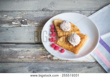 Crepes With Ice Cream With Chocolate Chips And Fresh Raspberries On Aged Wooden Background.