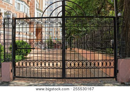 Large Black Gates Made Of Steel Rods And Wrought Iron Pattern On The Street
