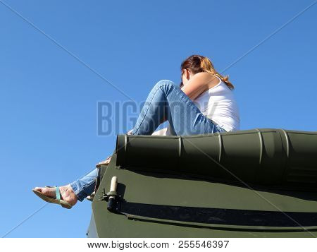 Girls In Jeans Sitting On The Armor Of An Armored Personnel Carrier Against The Blue Sky. Concept Of