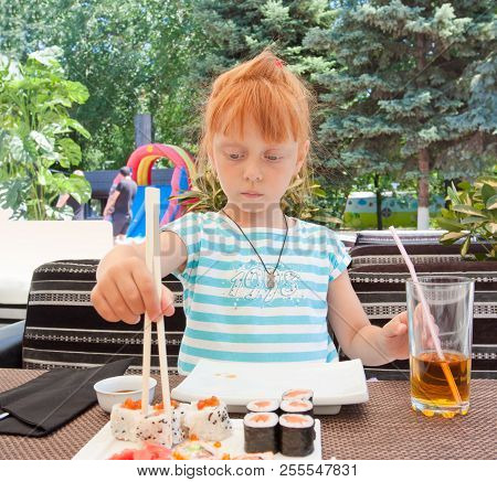 Beautiful Red-haired Girl In A Cafe. Child Eats Rolls And Sushi