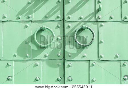 Metal green aged textured door with rings door handles and metal rivets. Metal architecture background.