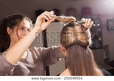 professional hairdresser making an unusual coiffure to a brown haired young model in a beauty salon poster