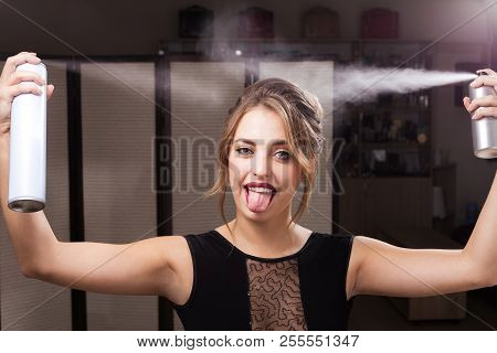 beautiful happy joyful model with perfect makeup and coiffure is fixationing her hair by two bottles of sprays. girl is showing a tongue. concept of professional hairdresser products poster