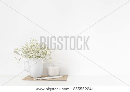 Background With Stationary, White Candle And Bouquet Of White Flowers In Mug On White Wall Backgroun