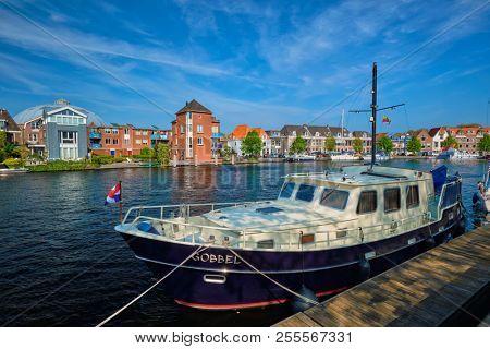 HAARLEM, NETHERLANDS - MAY 6, 2018: Spaarne river with boat moorned at quay in Haarlem, Netherlands