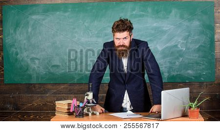 Teacher interesting interlocutor as authority. Teacher bearded man tell scary story. Teacher charismatic hipster stand near table classroom chalkboard background. Talking to students or pupils. poster