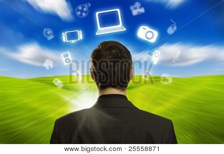 Young businessman with icons floating around his head