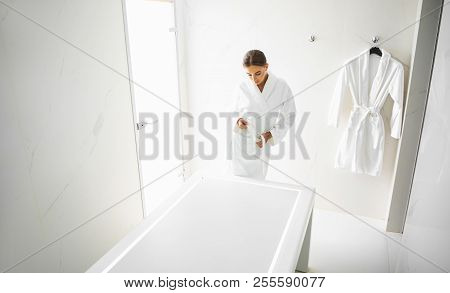 Serene Girl Standing At Massage Table And Tying Waistband