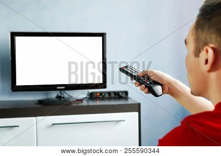 Tv Remote Control In Male Hand In Front Of Widescreen Tv Set With Blank Screen On Blue Wall Backgrou