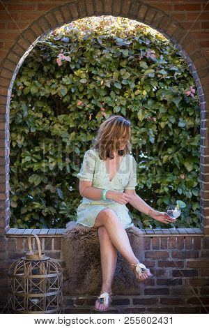 Beautiful Woman Sitting In A Arch Of A Frontporch With Gin Tonic
