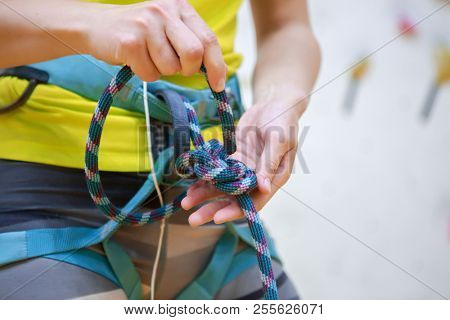 Close-up photo of athlete woman climber tying knot at gym