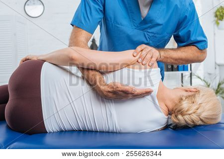 Cropped Shot Of Chiropractor Massaging Back Of Patient That Lying On Massage Table In Hospital