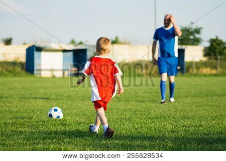 Little Soccer Boy In Red And Trainer In Blue Soccer Dress Are Playing Soccer On Playing Field, Socce
