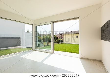 Large room with large bright windows overlooking the green lawn. Nobody inside