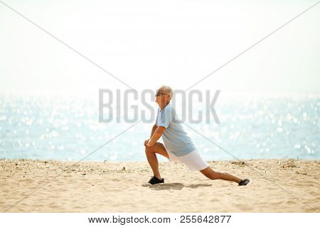 Senior man in activewear stretching his legs while exercising on sandy beach by waterside