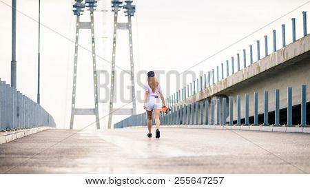 Young Beautiful Blonde Girl Walking Away with Orange Skateboard on the Bridge