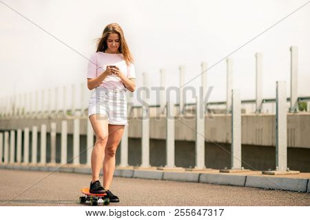 Young Beautiful Smiling Blonde Girl Using Smartphone on the Skateboard