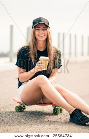Portrait of Young Beautiful Smiling Blonde Girl Drinking Coffee while Sitting on the Skateboard on the Bridge